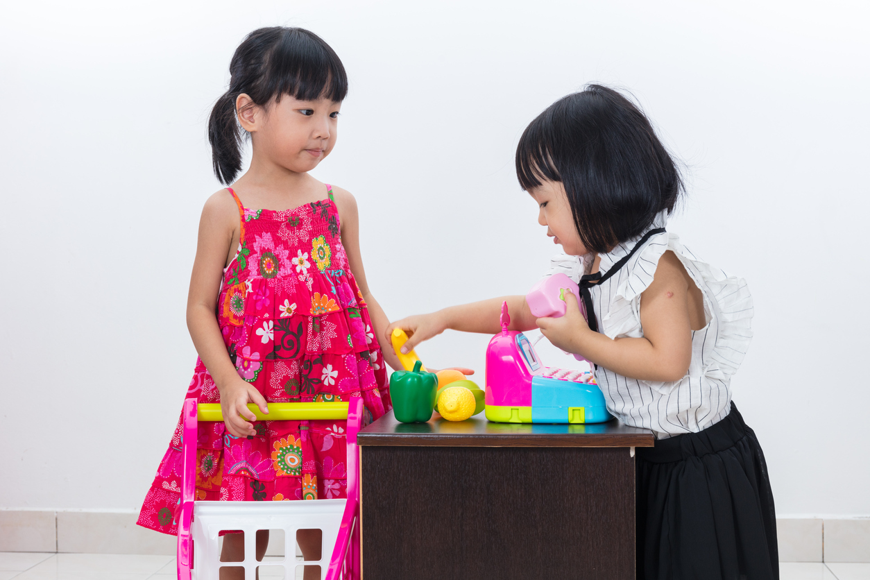 Asian Chinese little sisters pretending customer and cashier wit