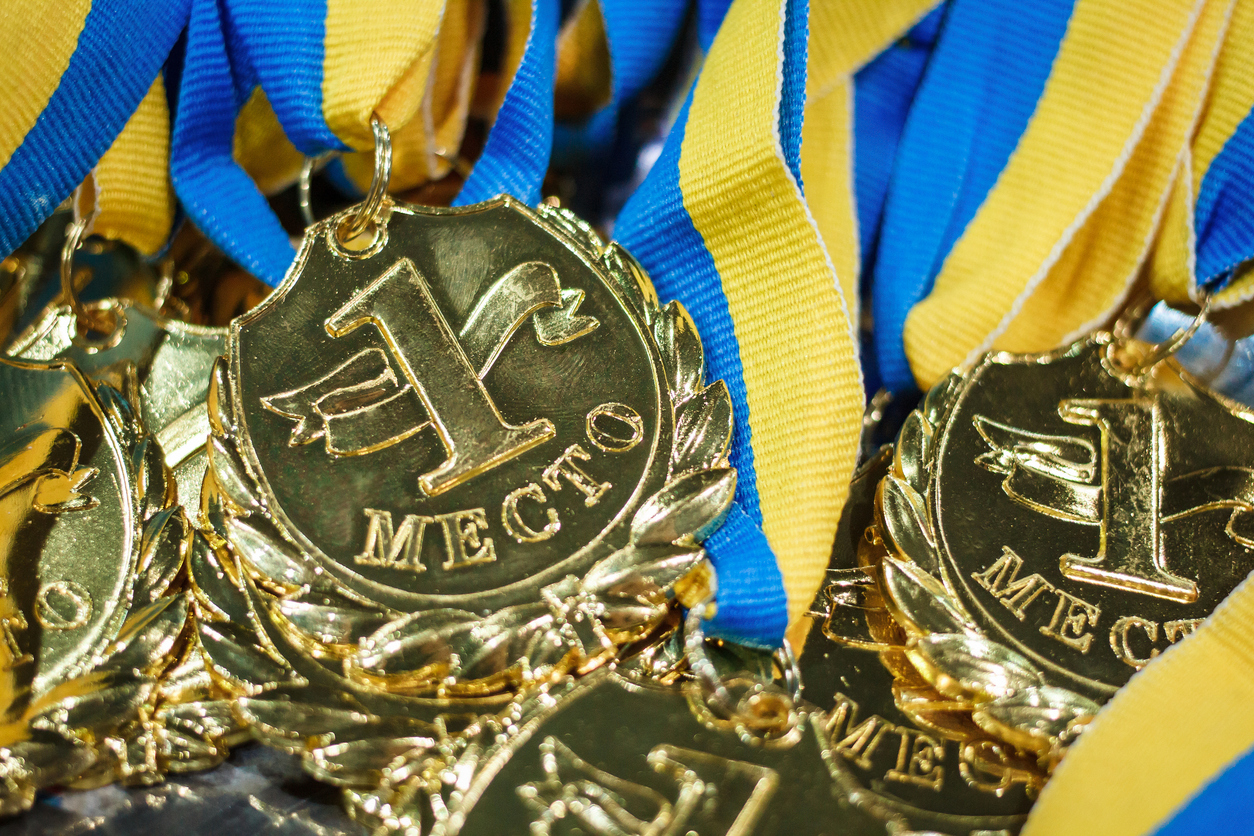 A lot of gold medals with yellow ribbons on a silver tray, awards of champions, sport achievements, first place, prize for the winner, it is written on a medal - first place