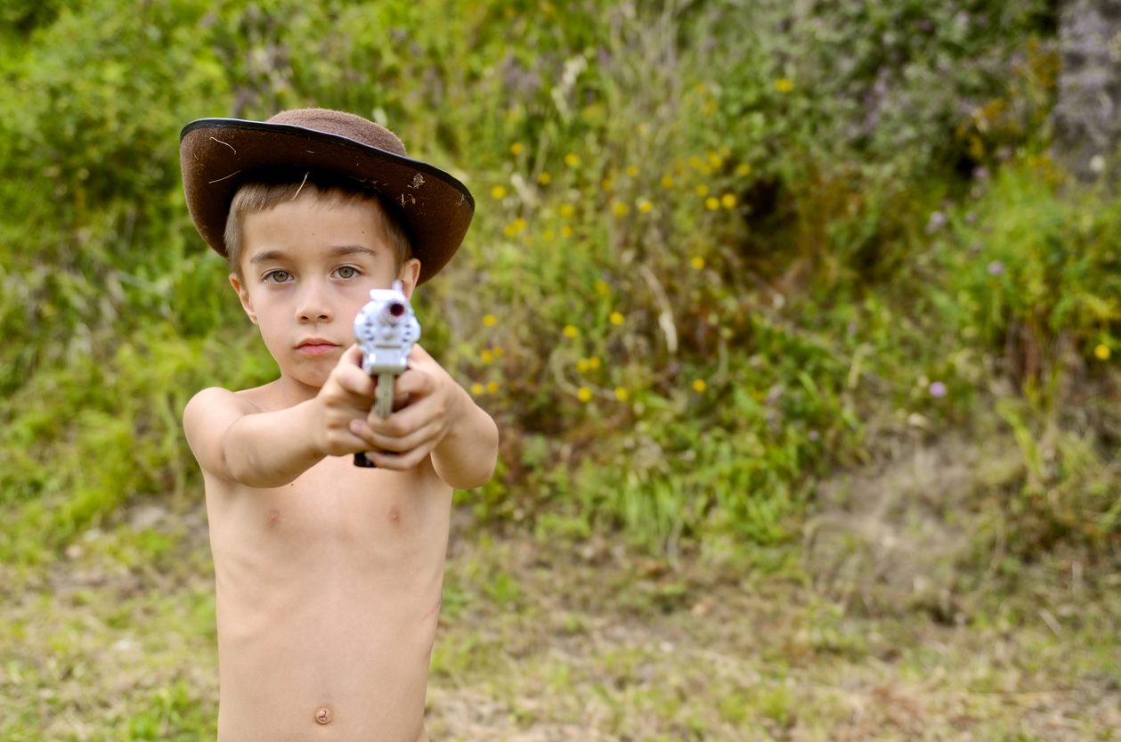 young kid with gun takes aim front to the camera
