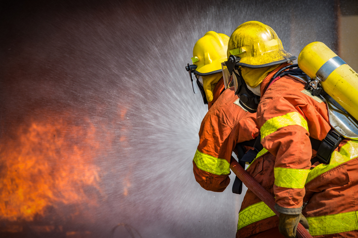 2 firefighters spraying high pressure water to  fire