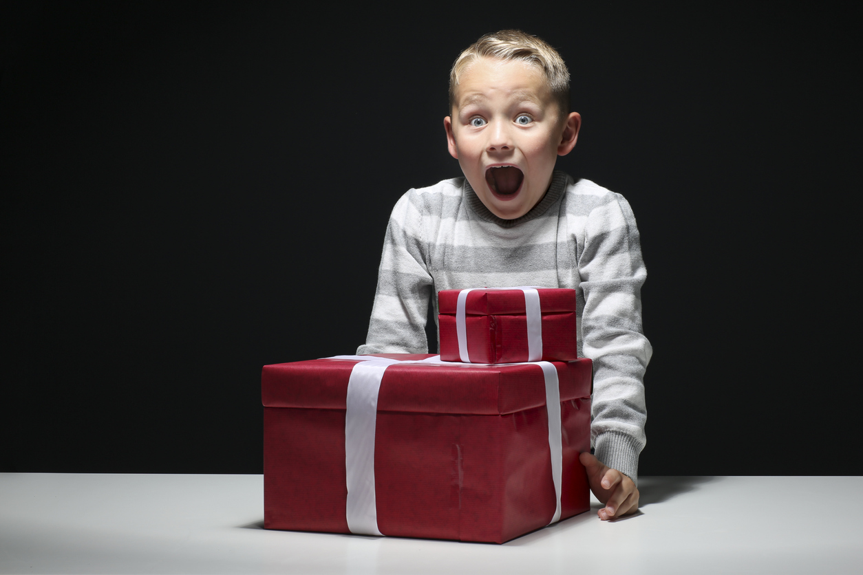 little boy with two presents is happy