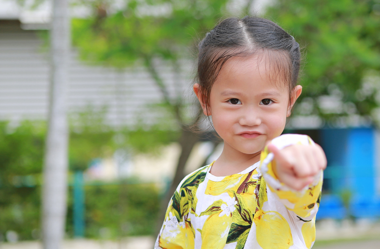 Little asian girl pointing at you with smile in the public garden.