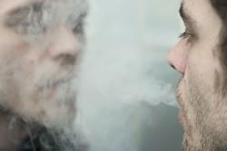 Man blowing smoke at his own reflection.