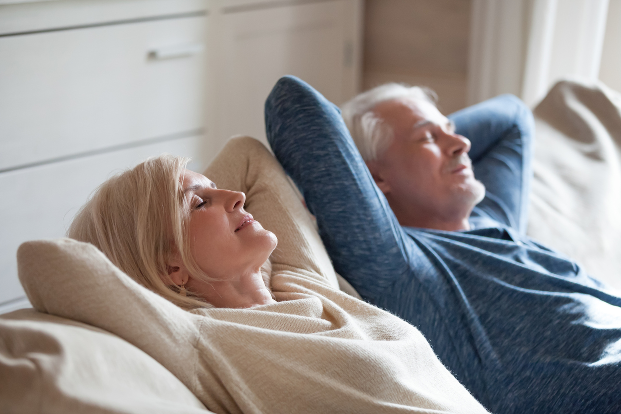 Calm mature couple relaxing on sofa having daytime nap together