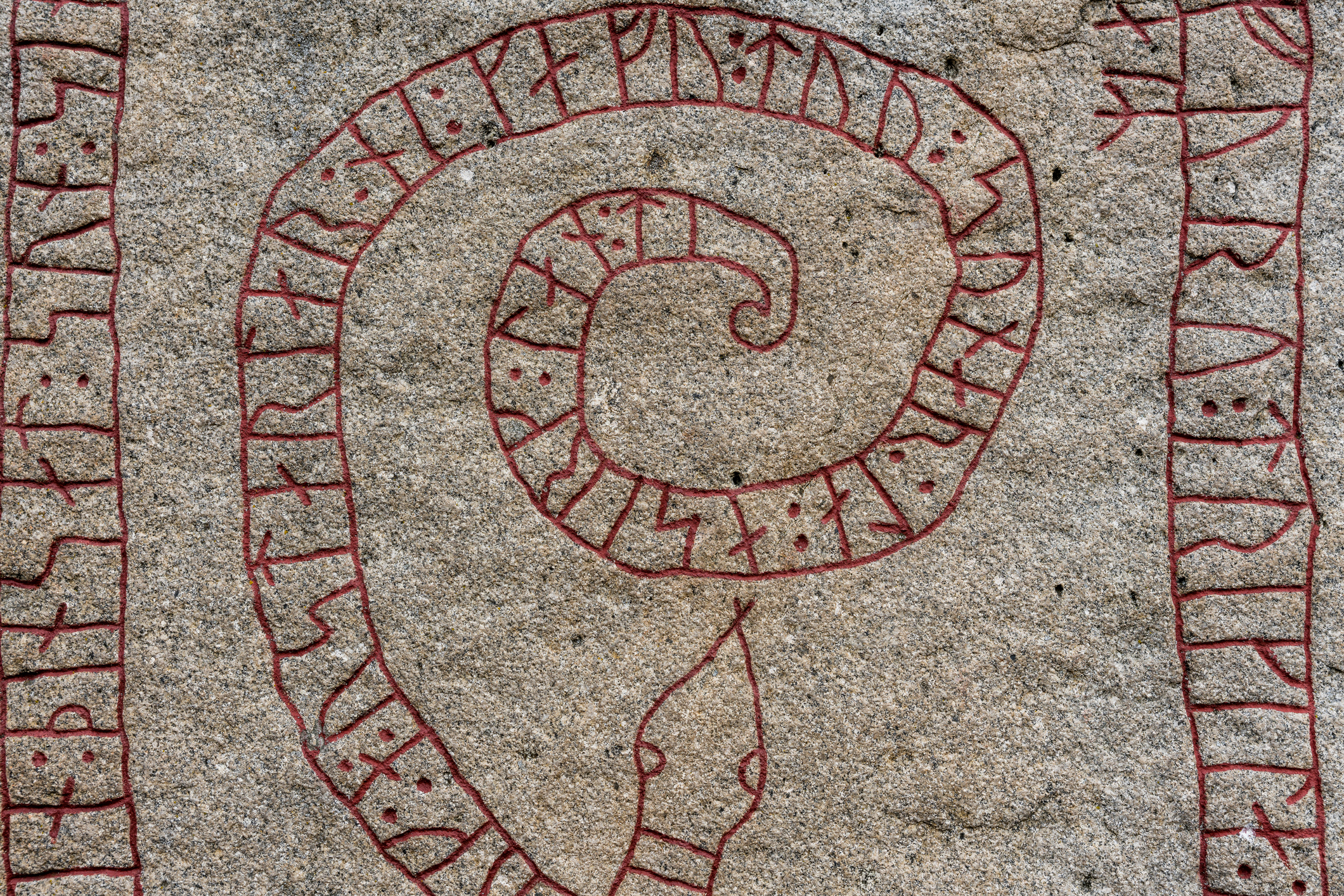 Close up of an old rune stone with red runes in the shape of a snake